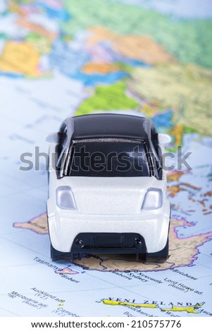 Back view of white, small, toy car on map. - stock photo