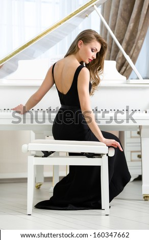 Back view of woman in black dress sitting and playing piano. Concept of music and art - stock photo