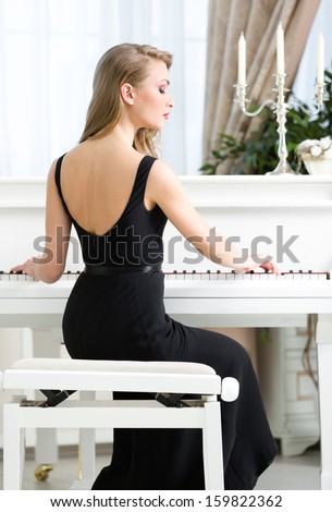 Back view of woman in black dress sitting and playing piano. Concept of music and enjoyment - stock photo