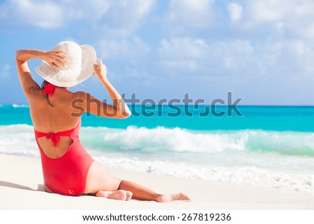 back view of woman in red swim suit and straw hat sitting on tropical beach