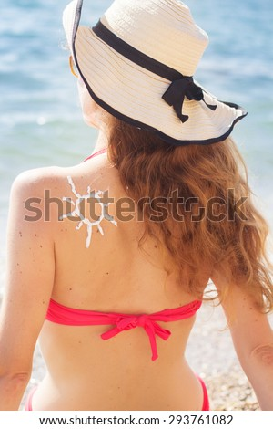 Back view of woman is wearing hat with sun tan lotion sun drawing  - stock photo