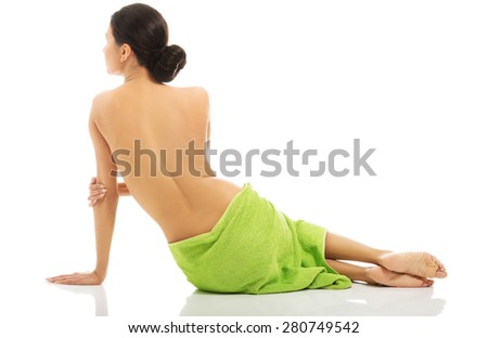 Back view of woman lying wrapped in green towel - stock photo