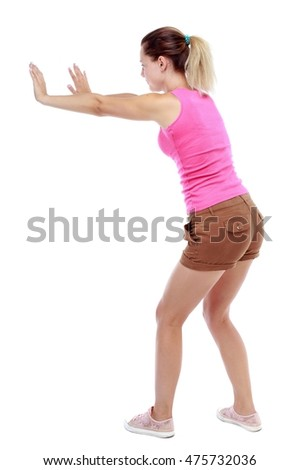 back view of woman pushes wall. Isolated over white background. Sport blond in brown shorts shows stop sign.