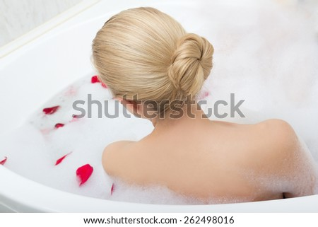 back view of woman relaxing in bubble bath with red flower petals - stock photo