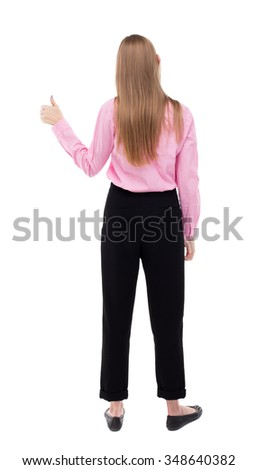 Back view of  woman thumbs up. Rear view people collection. backside view of person. Isolated over white background. The girl office worker in black trousers shows thumb up with his left hand. - stock photo