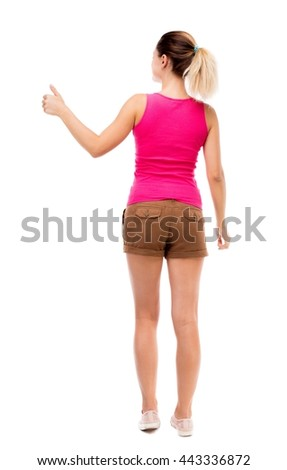 Back view of  woman thumbs up. Rear view people collection. backside view of person. Isolated over white background. Blonde girl in shorts and a pink blouse is showing the right hand thumb up. - stock photo