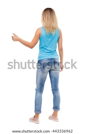 Back view of  woman thumbs up. Rear view people collection. backside view of person. Isolated over white background. blonde in a blue t-shirt and jeans with his right hand shows the thumb. - stock photo