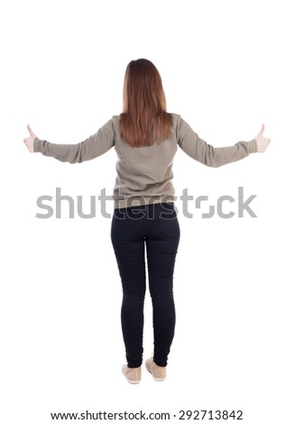 Back view of  woman thumbs up. Rear view people collection. backside view of person.   Two hands girl in a gray jacket shows the big finger. - stock photo