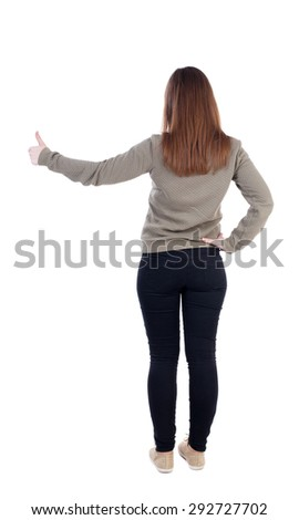 Back view of  woman thumbs up. Rear view people collection.   slender blonde in a jeans shows the symbol of success or hitchhiking. left-handed girl in a gray jacket shows the big finger. - stock photo