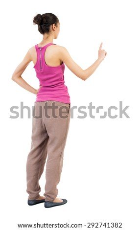 back view of woman. Young woman presses down on something. Isolated over white background.  African-American woman standing sideways with his hand in his pocket a second hand presses. - stock photo