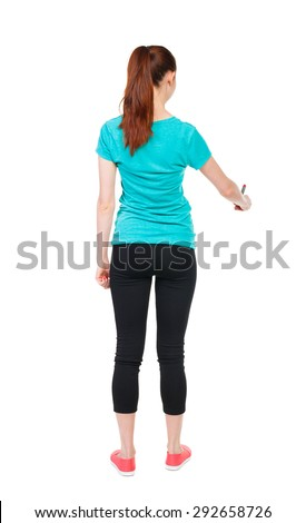 back view of writing beautiful woman. Young girl in sweatpants. Rear view people collection. backside view person. Isolated over white background. Sports girl draws felt-tip pen at bottom of something - stock photo