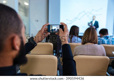 Back view of young african man making video with smartphone on business conference in meeting room - stock photo