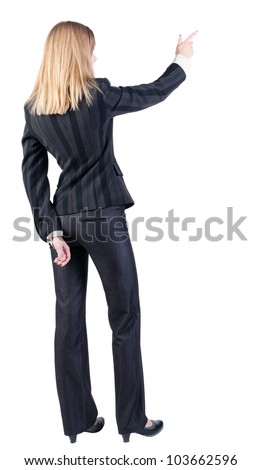 Back view of young blonde business woman pointing at wall . beautiful girl in dark suit. Rear view people collection. backside view of person.  Isolated over white background. - stock photo