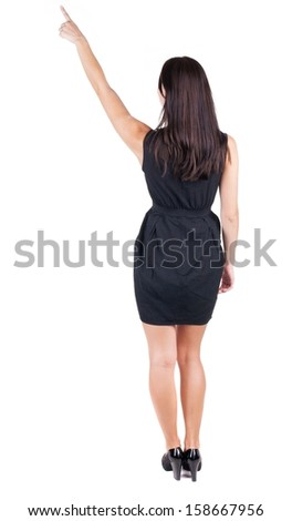Back view of young brunette woman pointing at wall. beautiful girl in black dress. Rear view people collection. backside view of person. Isolated over white background. - stock photo