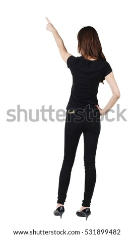 Back view of young brunette woman pointing at wall . beautiful girl in black jeans showing gesture. Rear view. Isolated over white background.