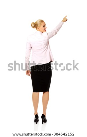 Back view of young business  woman pointing for somathing - stock photo