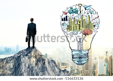 Back view of young businessman standing on mountain top next to creative financial sketch inside light bulb. Business idea and leadership concept