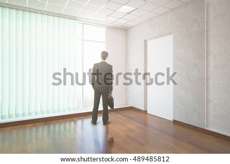 Back view of young businessman with briefcase standing in unfurnished interior with wooden floor and panoramic windows with blinds. 3D Rendering