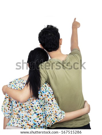Back view of young couple pointing at wall. Isolated over white background - stock photo