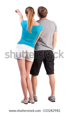 Back view of young couple pointing at wall (woman and man). Rear view people collection.   backside view of person.  Isolated over white background. by summer dressed teenagers refer to something far - stock photo
