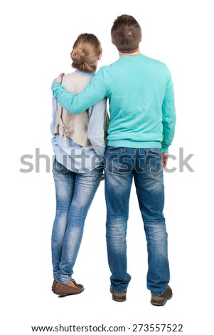 Back view of young embracing couple (man and woman) hug and look into distance. Rear view people collection. .  Isolated over white background. Guy hugs the girl in the shoulder vest. - stock photo