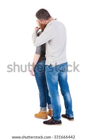 Back view of young embracing couple (man and woman) hug and look into the distance. beautiful friendly girl and guy together. The guy behind hug his wife.