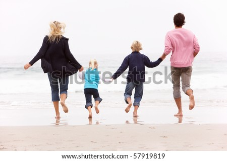 Back View Of Young Family Running Along Winter Beach