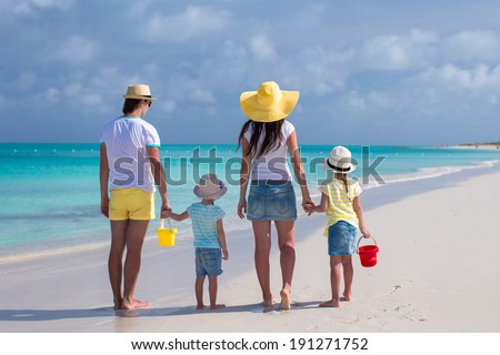 Back view of young family with two kids on caribbean vacation - stock photo