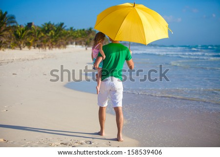 Back view of Young father and his little daughter hiding from the sun under a yellow umbrella - stock photo