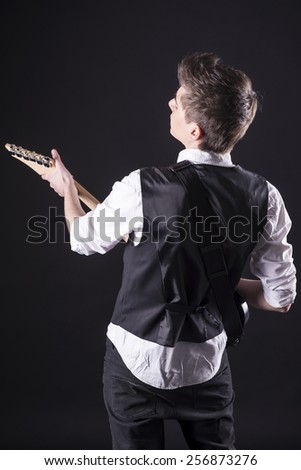 Back view of young guitarist with the electric guitar, isolated on dark background. - stock photo