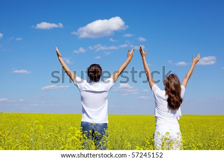 Back view of young guy and girl praising God in yellow meadow at summer