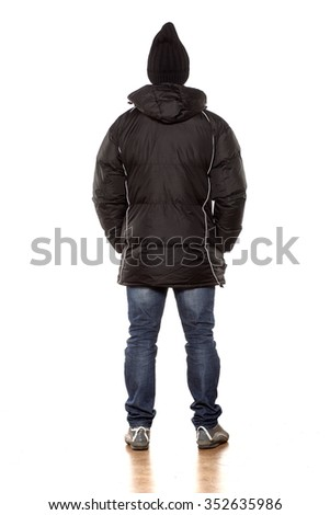 back view of young handsome man posing with winter jacket  - stock photo