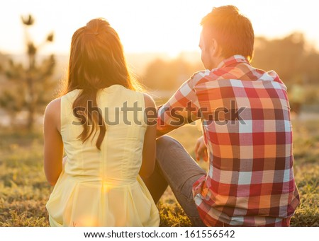 back view of young happy couple sitting on river at sunset - stock photo