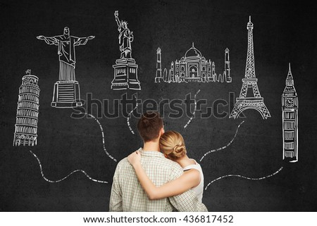 Back view of young honeymoon couple looking at sights sketches on dark concrete background. Travel concept
