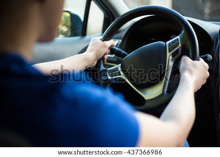 back view of young male driver holding steering wheel - stock photo