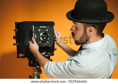 back view of young man in hat as photographer with retro camera on an orange background - stock photo