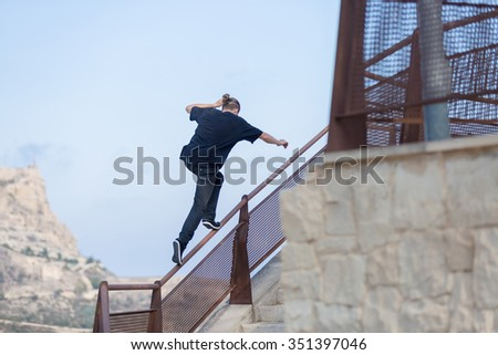 Back view of young man jumping on railing