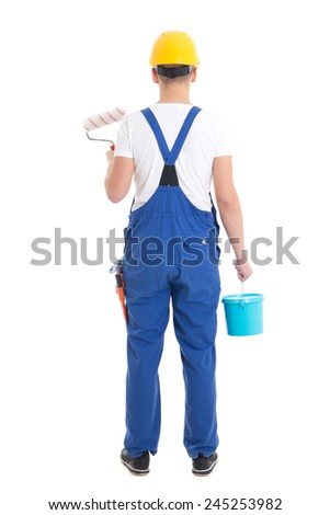 back view of young man painter in blue coveralls isolated on white background - stock photo