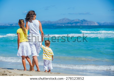 Back view of young mother with her two kids on tropical beach vacation - stock photo