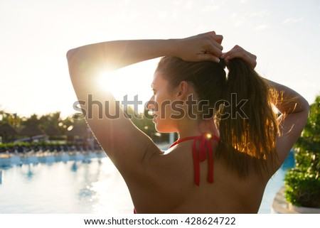 Back view of young woman getting ready for sunbathing and enjoying vacation at tropical caribbean resort swimming pool. Brunette female tying ponytail at poolside towards the sunrise.