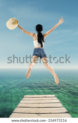 Back view of young woman holding a hat and jump on the pier to enjoy her holiday - stock photo