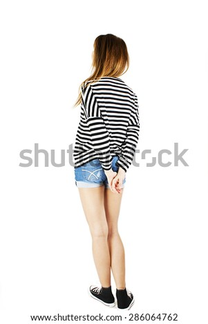 Back view of young woman in denim shorts and striped sweatshirt looking at wall. The rear view. Isolated on white background.  - stock photo