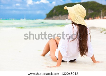 back view of young woman in straw hat on tropical beach - stock photo