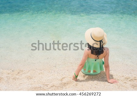 back view of  young woman in swimsuit and straw hat on tropical andaman beach.holiday and relaxing time in vocational. - stock photo