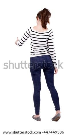 back view of young woman presses down on something. Isolated over white background. Rear view people collection. backside view of person. Girl in white striped jacket presses a finger in front of him.