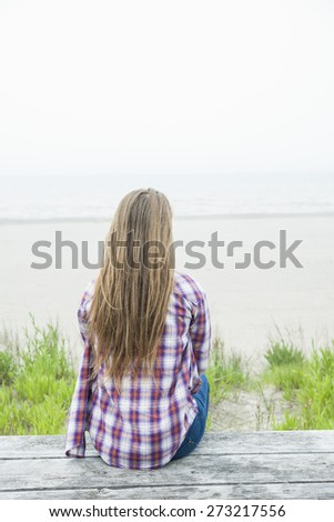 Back view of young woman with long blond hair sitting on old beach picnic table facing ocean wearing plaid shirt - stock photo