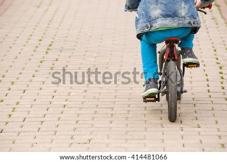 Back view on a kid boy riding on a small bicycle in the park. Child on the bike on asphalt road. Children activities outdoors. - stock photo