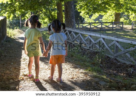 Back view on two little sisters walking in park together while holding hands at sunny day. Unrecognizable - stock photo
