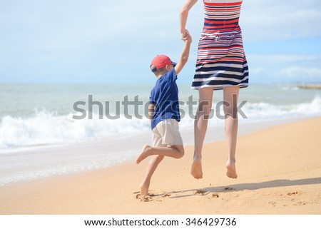 Back view photo of happy mother and her excited son having fun running along sandy shore and holding hands