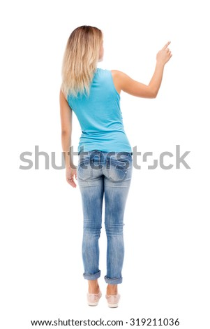 Back view pointing woman. beautiful girl. Rear view people collection.  backside view of person.  Isolated over white background. The girl in jeans and a blue shirt shows a finger of his right hand. - stock photo